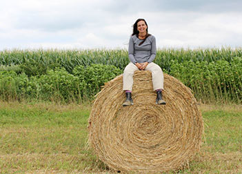 Linda sitting on hay bale