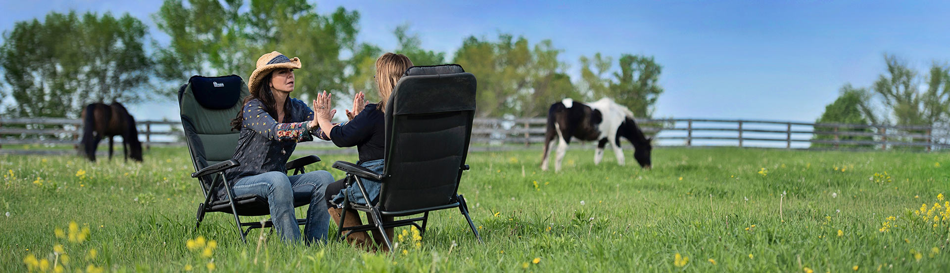 Two women sitting in pasture